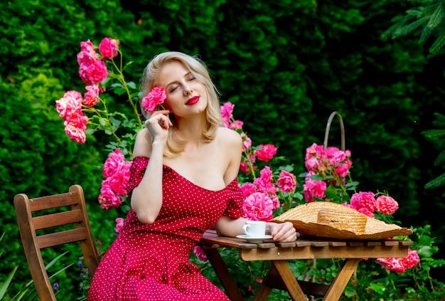 Красивая блондинка в красном платье пьет кофе в саду