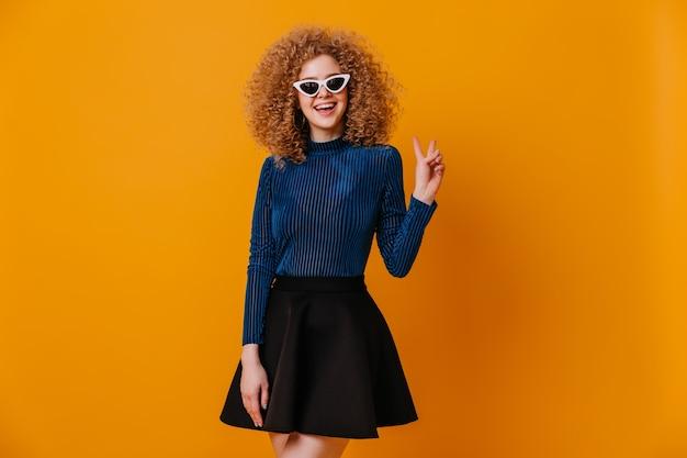 Красивая блондинка в полосатой синей блузке и стильной юбке улыбается и показывает знак мира на желтом пространстве.