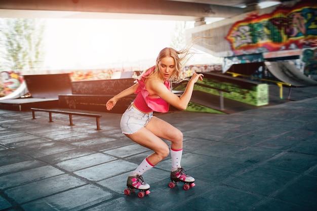 아름다운 금발 소녀는 롤러 블레이드 동안 몇 가지 트릭을하고 있습니다. 그녀는 쪼그리고 앉은 자세로 서서 아래를 내려다보고 있습니다. 그녀의 손은 몸 옆에 있습니다. 그녀는 훈련실에서 운동하고 있습니다.