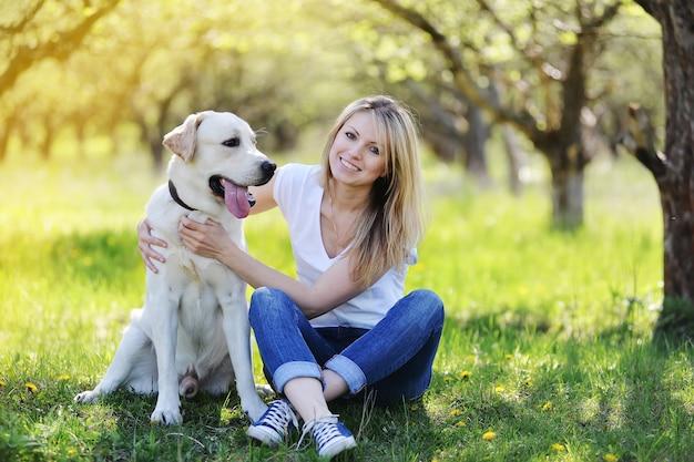 Красивая блондинка гуляет со своим домашним лабрадором в парке весной.