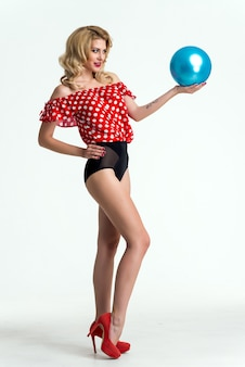 Красивая блондинка девушка, изолированных на светлом фоне в студии с голубой шар