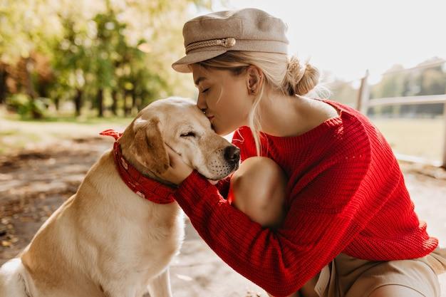 秋の日当たりの良い公園で彼女の愛らしい犬にキスする美しいブロンドの女の子。ペットを優しく抱きしめる赤いセーターと流行の帽子のスタイリッシュな若い女性。