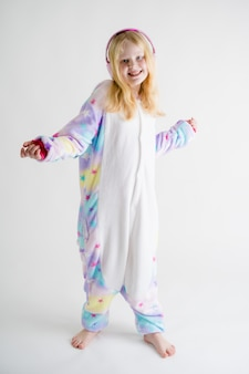 Beautiful blonde girl listens to music with headphones on white in kigurumi pajamas