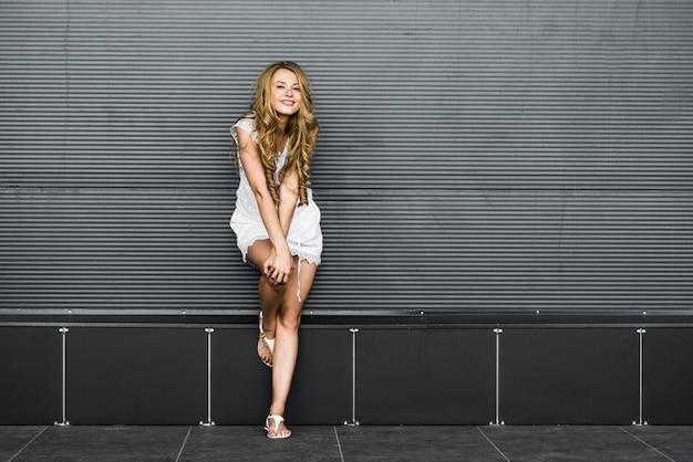 灰色の壁の近くの美しいブロンドの女の子