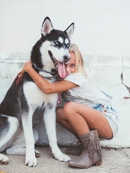 Красивая блондинка позирует с питомцем сибирской хаски