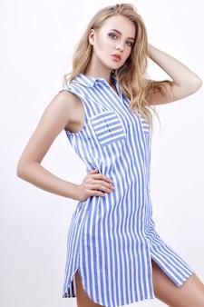 Красивая блондинка позирует в летней одежде