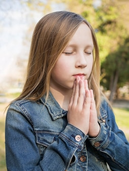 祈っている美しいブロンドの女の子