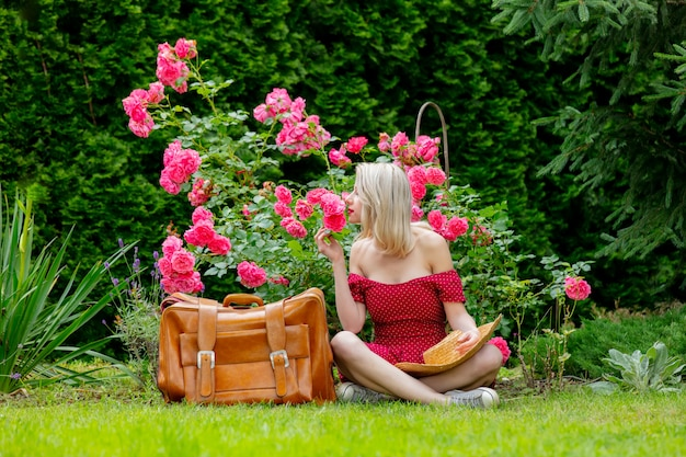 Beautiful blonde girl in red dress with suitcase in a garden