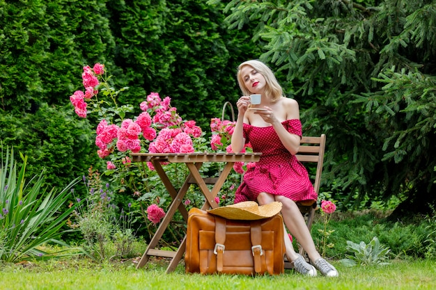 Beautiful blonde girl in red dress with suitcase is drinking a coffee in a garden