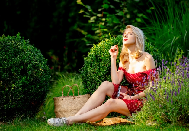 Beautiful blonde girl in red dress with vintage camera in a garden