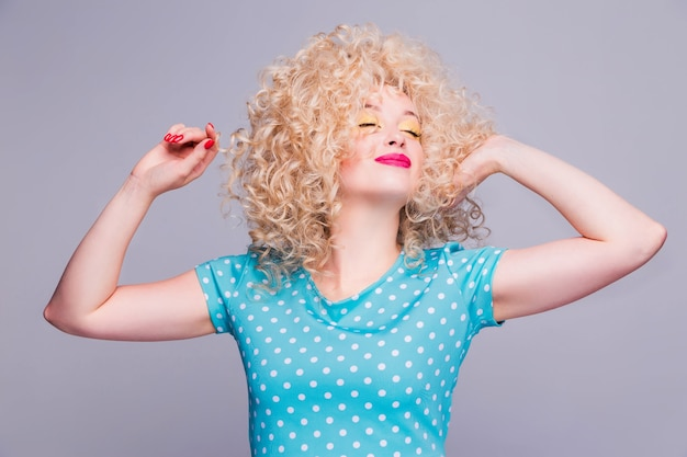 Beautiful blonde girl in retro style with voluminous curly hairstyle, in a blue polka-dot blouse on gray