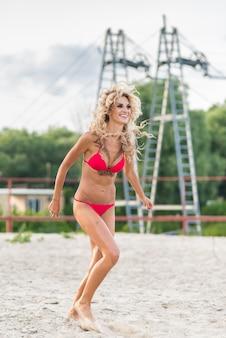 Beautiful blonde girl running on the beach