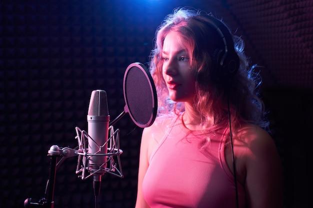 Красивая блондинка поет песню в студии звукозаписи с профессиональным микрофоном и наушниками, создает новый трек-альбом, вокалист в розово-синем неоновом свете, лицо крупным планом, караоке