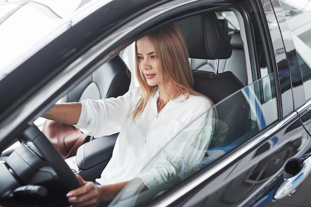 モダンな黒のインテリアで新しい車に座っている美しいブロンドの女の子