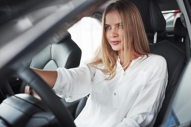 현대 블랙 인테리어와 새 차에 앉아 아름 다운 금발 소녀