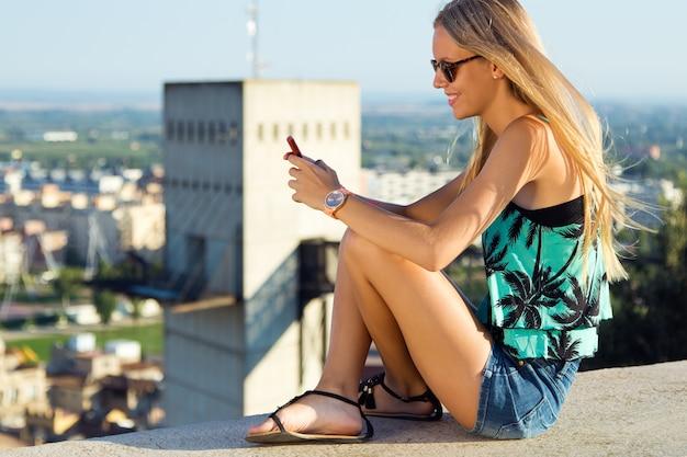 Bella ragazza bionda seduta sul tetto con il telefono cellulare.