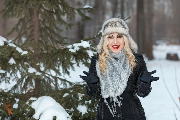 木の近くの冬の森に立っている美しいブロンドの女の子