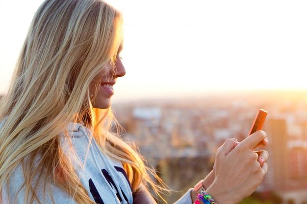 美しいブロンドの女の子が街の写真を撮っています。