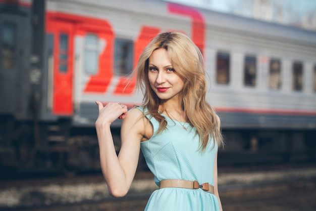 Beautiful blonde girl waiting for the train at the station
