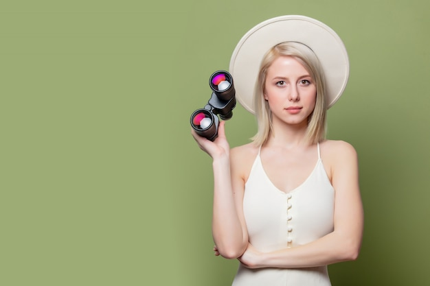 Beautiful blonde girl in a white hat and dress with binoculars