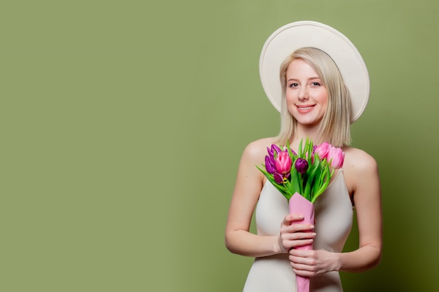Beautiful blonde girl in white hat and dress with tulips
