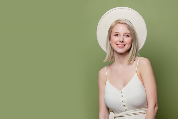 Beautiful blonde girl in white hat and dress