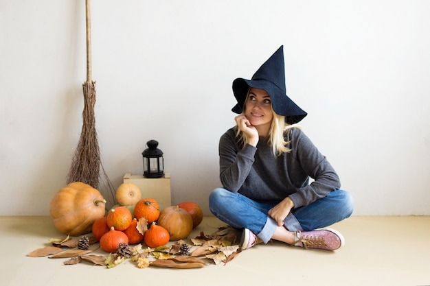 Beautiful blonde girl in a witch hat with pumpkins and a broom on white