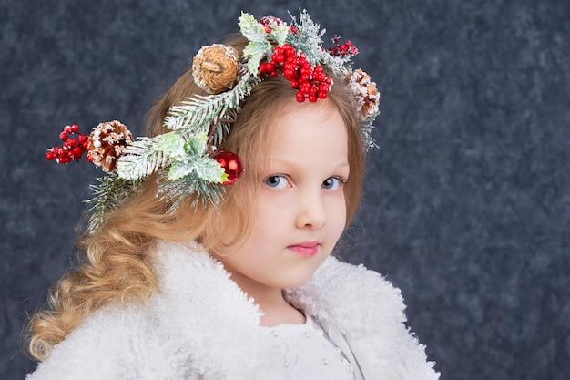 회색 배경에 머리에 크리스마스 화환을 얹은 아름다운 금발 소녀