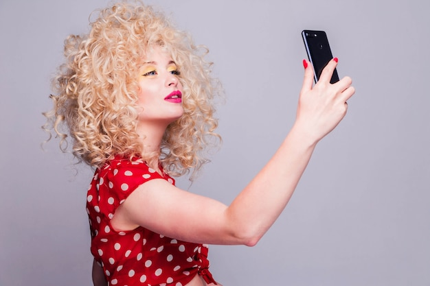 Красивая блондинка с кудрявой прической, ярко-желтым макияжем и красной блузкой в горошек делает селфи