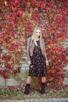 秋の美しいブロンドの女の子の葉ブドウの肖像画