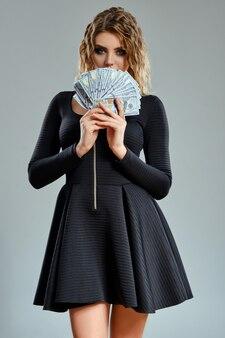 Красивая блондинка с вьющимися волосами и ярким макияжем, в черном коротком платье прикрыла рот деньгами.