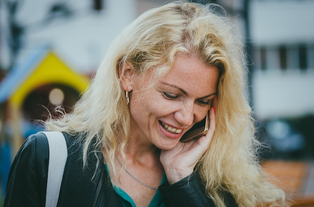街でスマートフォンで話している巻き毛の美しいブロンドの女の子。フリーランサーの仕事、仕事の瞬間の決定。