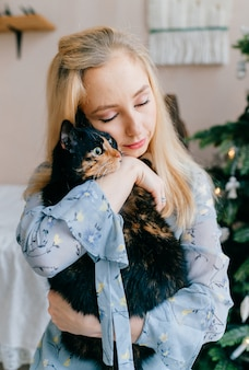 . beautiful blonde girl with kind tender face hugging little purebred domestic pet.