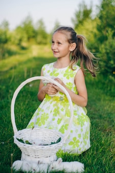 Beautiful blonde girl with little rabbits sitting in the green grass. holiday rabbits. easter bunny