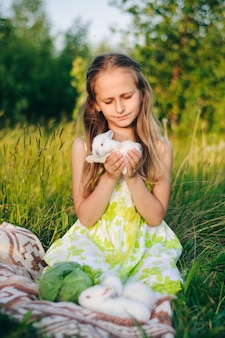 Beautiful blonde girl with little rabbits sitting in the green grass