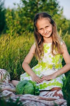 の芝生に座っている小さなウサギと美しいブロンドの女の子。休日のウサギ。イースターのウサギ