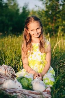 の芝生に座っている小さなウサギと美しいブロンドの女の子。 y