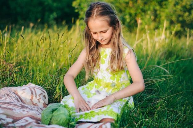 の芝生に座っている小さなウサギと美しいブロンドの女の子。