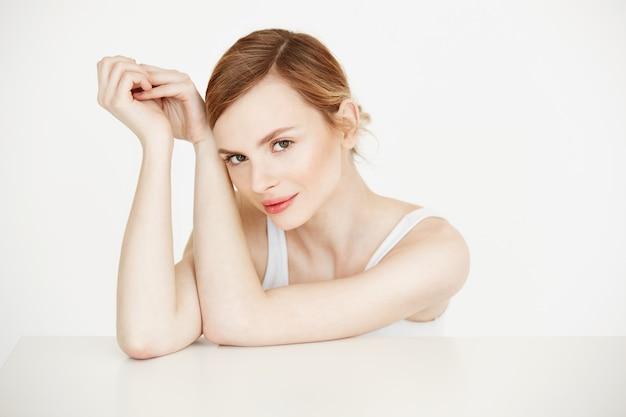 Bella ragazza bionda con seduta sorridente perfetta pelle pulita al tavolo. cosmetologia. trattamento facciale.