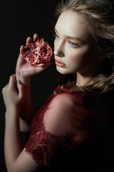 Красивая блондинка с фруктами граната в руке