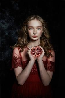 Красивая блондинка с гранатовым фруктом в руках.