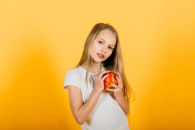 Красивая блондинка с красным яблоком в студии, желтый фон