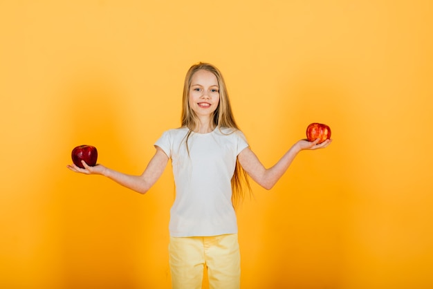 Beautiful blonde girl with red apple in studio, yellow background