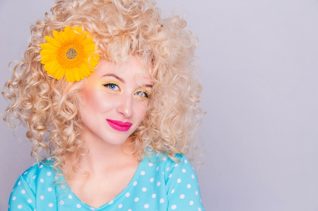 Beautiful blonde girl with voluminous curly hairstyle, in a blue polka dot blouse