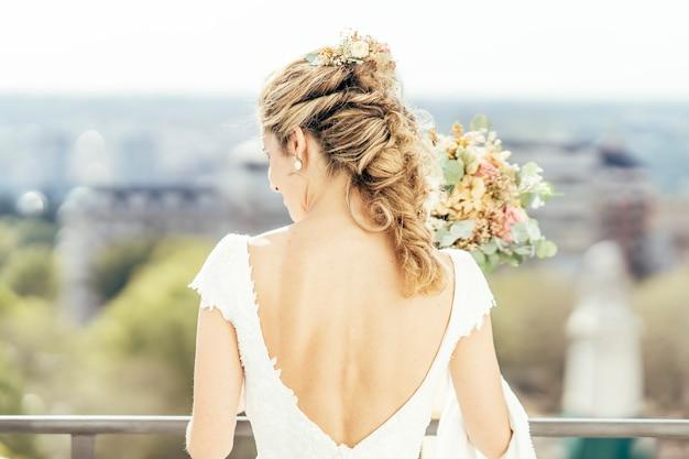 結婚する前に彼女の結婚式の日に白い服を着た美しいブロンドの髪の女性。