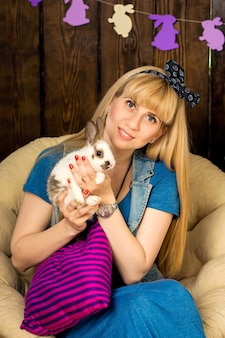 Beautiful blonde holding a cute fluffy white rabbit in her hands. easter celebrations.