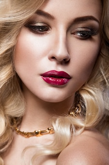 Beautiful blonde in a hollywood manner with curls, red lips