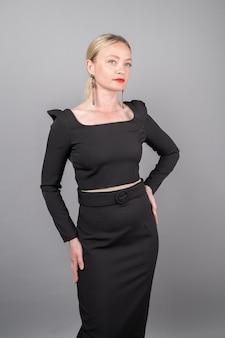 孤立した背景に黒いドレスを着た美しいブロンド。