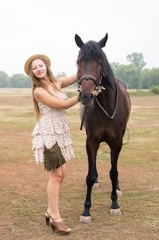 밀짚 모자와 여름 드레스에 아름다운 금발은 말과 함께 촬영