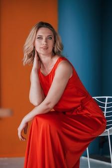 축제 빨간 드레스의 아름다운 금발은 주황색과 파란색 벽과 흰색 의자가있는 방에 있습니다.